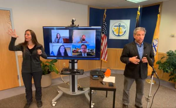 A ASL interpreter signs on the left, a screen with four faces in the middle, and Berkowitz on the right.