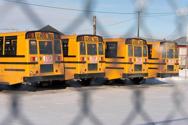 Yellow school buses as seen through a chain link fence in snow-covered ground