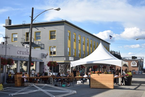People eat outside on a blocked off section of G St. A white tent is set up in the middle of the street.