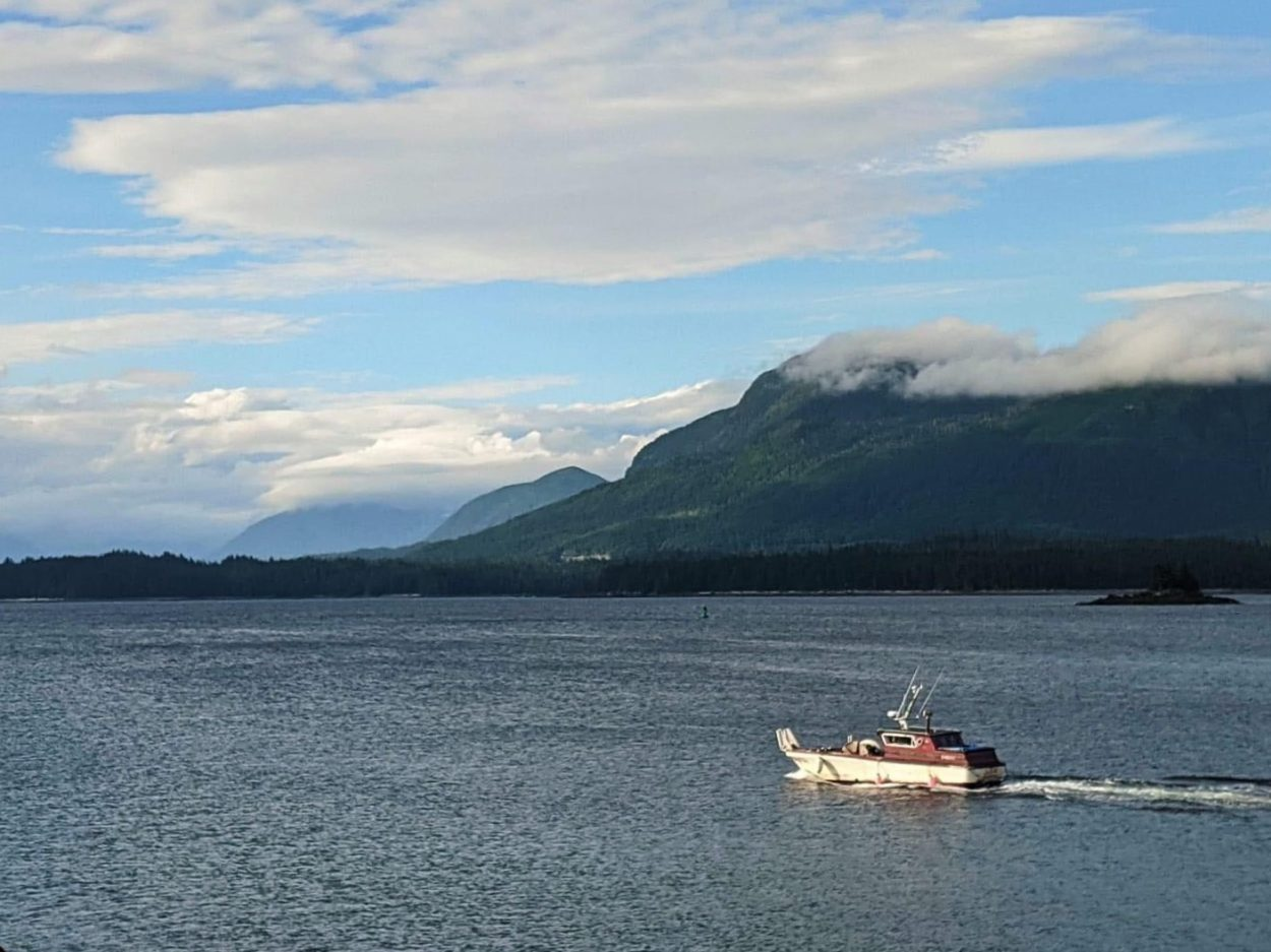A 32-foot gilnetter sails in blue waters next to green spruce-covered mountains.