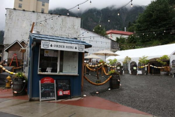 """A small blue food stand in an open outdoor gravel-laden food court with a sign that says """"order here"""" above the window."""