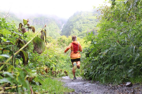 A runner bounds down a wet dirt trail wearing black shorts, a red backpack and an orange windbreaker. Mountains rise into mist in the background and there are wet leaves and other vegetation in the foreground.