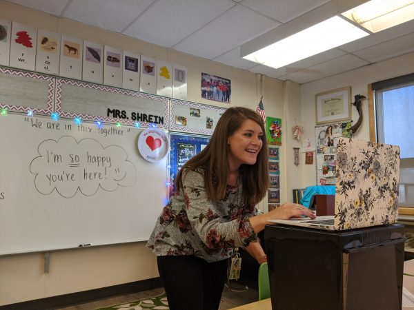 A woman smiles and bends over to look at her laptop screen in her 5th grade classroom