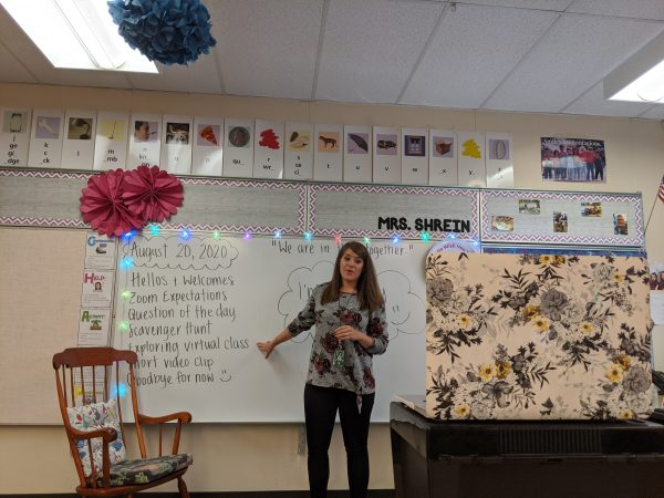"""A woman points her laptop camera towards herself and points to the words """"Exploring Virtual Class"""" on a whiteboard in her classroom"""
