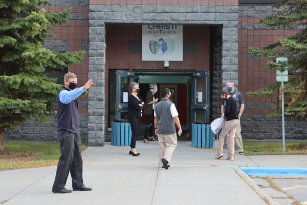 Staff greets a student and parent outside of Lumen Christi Catholic High School. Everyone is wearing a face covering. It's the second day of school.