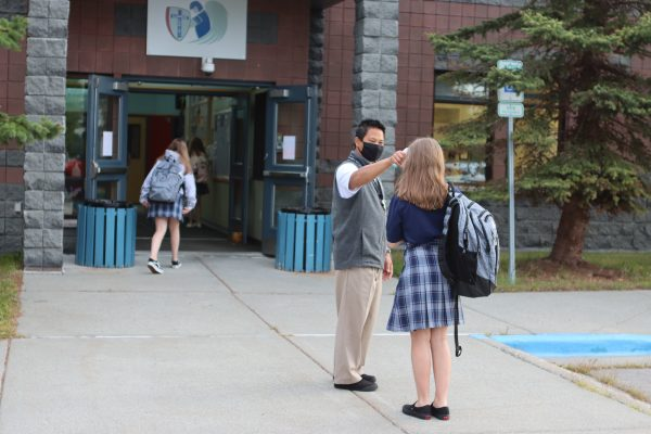 Michael Bauzon, a teacher and dean of student affairs at Lumen Christi High School, takes a student's temperature outside on Tuesday, Aug. 18, 2020. The small Catholic school is among a handful of private schools in Anchorage holding in-person classes. Tuesday was the second day of the school year.