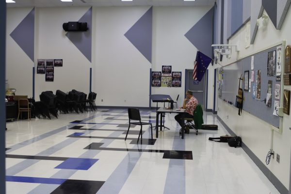 East High School teacher Kiel Schweizer talks to his guitar students over the computer. He's sitting in the school's large, vacant band room.
