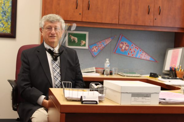 East High School Principal Sam Spinella sits behind his desk wearing a face shield.