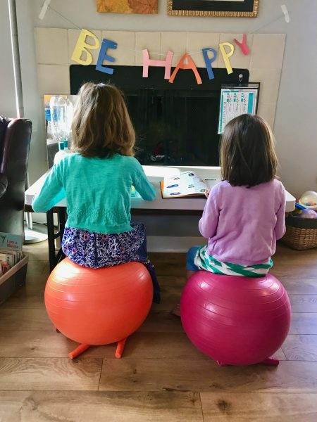 Two girls sit on inflatable balls while working on laptops