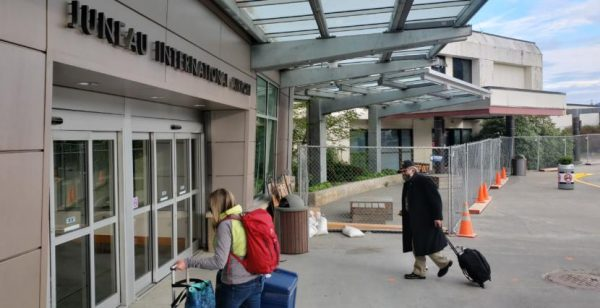 Two people carry luggage towards the sliding glass doors under an awning at the Juneau Airport