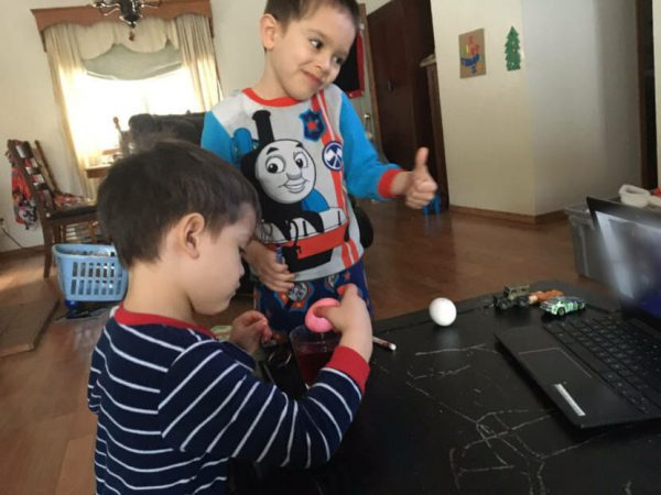 Two boys play with toys on a table at a home. One boy is weraing a blue train shirt and is giving a thumbs up.