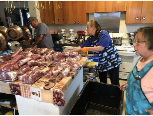 Several Alaska Natives work on processing meat in a kitchen.