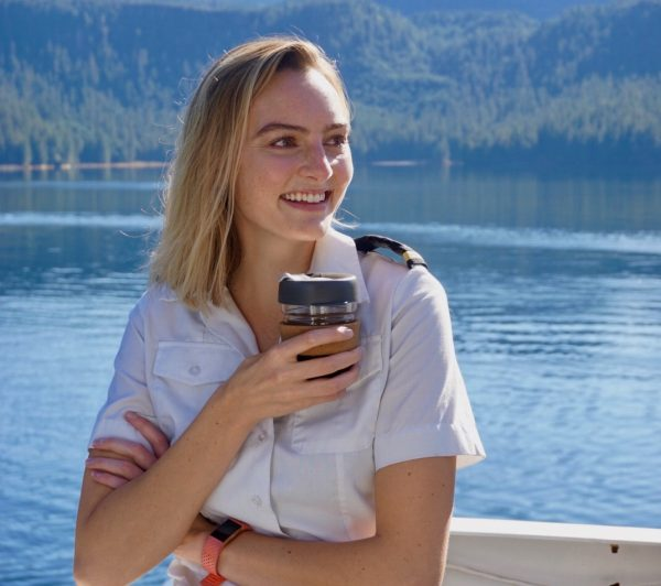 A woman in a white shirt with black epaulettes holds a cup and smiles. She's on a boat deck in calm water. Forested slopes are in the background.