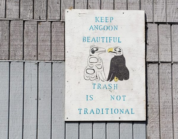 "A white sign on a wall says ""Trash isn't traditional/Keep Angoon beautiful)"