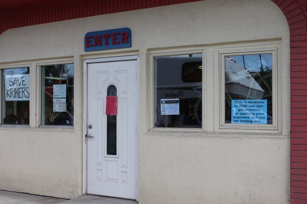 """One of the entries atKriner's Diner in Anchorage. The Municipality of Anchorage posted the red sign on the door ordering the restaurant to shut down dine-in service. To the left, another sign reads: Save Kriner's"""" and to the right one says: """"Only in America in 2020 can you get arrestedfor openingyour business, but not for looting one..."""""""