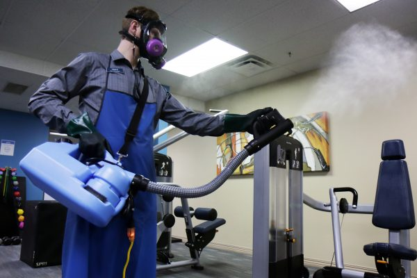 Joshua Easterly, operations manager at Alaska Club East, uses a disinfectant fogger to clear the gym.
