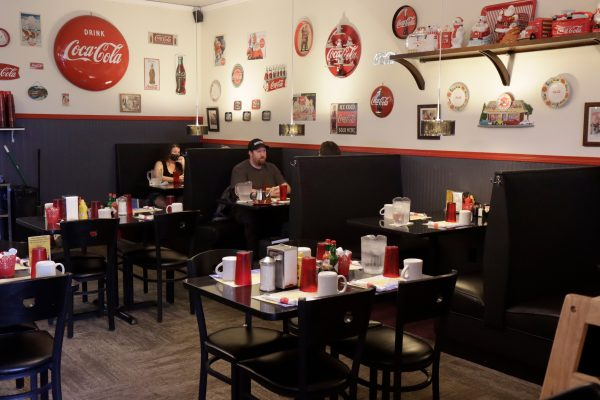 Two patrons at a booth in Little Dipper Diner. Several empty tables and booths surround the patrons