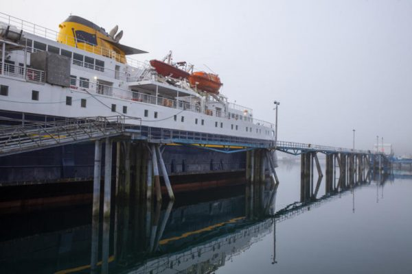 A blue ferry with white cabin pulls up next to an elevated dock on a foggy day.