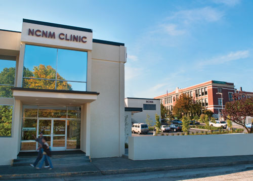 Two students walk past the 'NCNM Clinic' building in Portland, Ore.