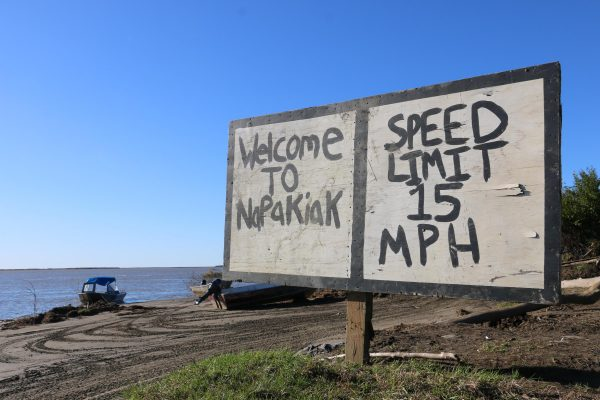 """A hand-painted piece of plywood stands over lookign the water. It reads """"Welcome to Napakiak - Speed Llimit 15 MPH"""""""