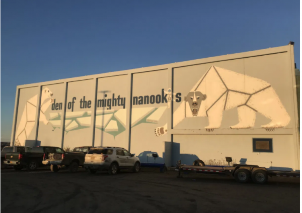 """""""home of the Nanooks"""" is written on the wall of a school with a geometric polar bear paiinnted on the wall"""