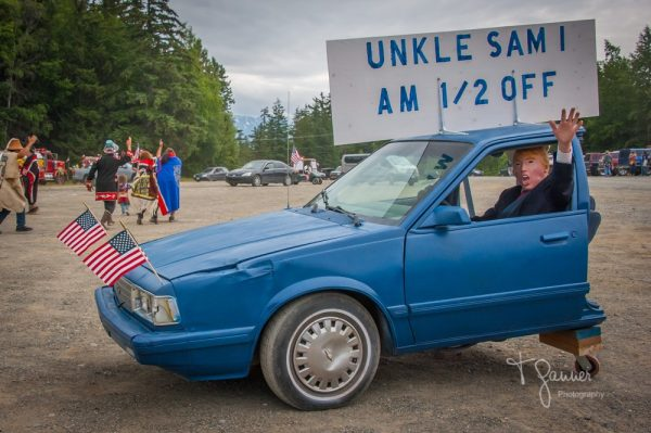 """A man in  a trump mask holds a sign up through the window of the front half of a blue sedan. The sign says """"Uncle Sam I am 1/2 off"""""""