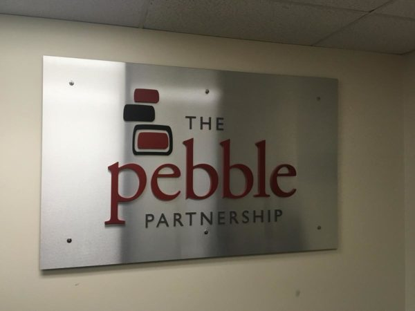 """A silver sign that reads """"The Pebble Partnership"""""""