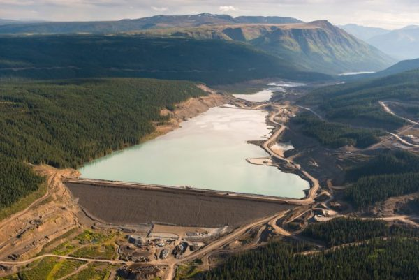 An aerial shot of a massive dam holding in mine tailings surrounded by spruce forests and rolling hills.