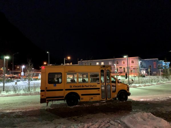 A yellow shuttle waits in a snowy parking lot
