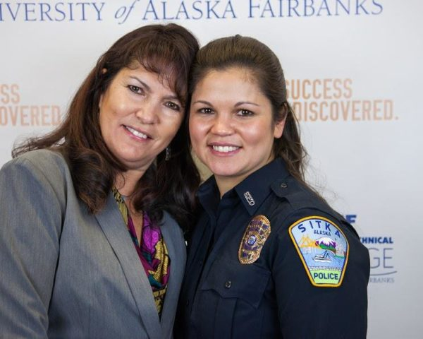 Two brown haired women, one in a gray suit and one in a blue police uniform