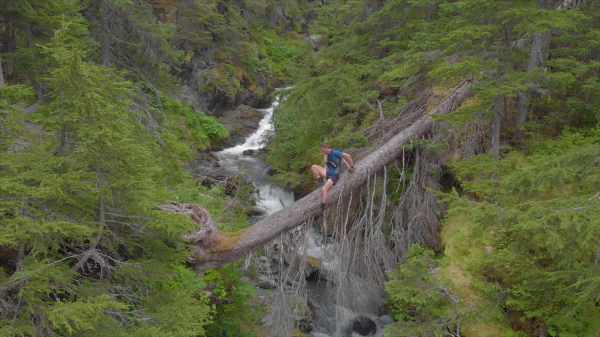 A man crawls on his back over a tree that has fallend over a raging creek