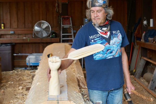 A man in a blue tshirt, bandana, with gray hair and a goattee holds a sculpture of a hand holding a feather in a wood shop