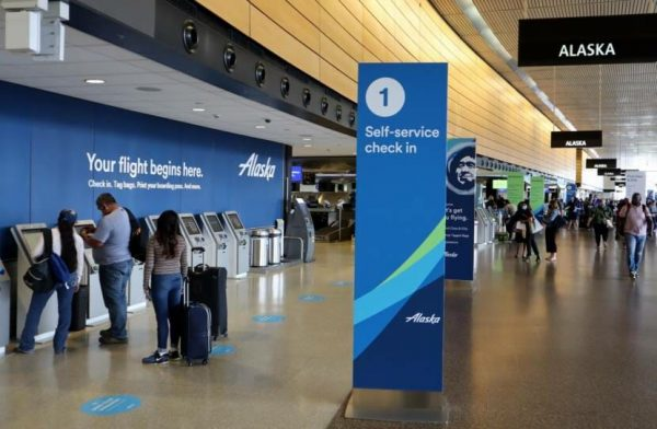 Passengers check in at one of about a half dozen kiosks next to blue Alaska Air banners