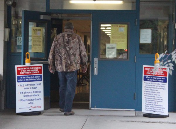 A man in a camoflauge jacket and jeans walks through blue doors with notices about health warnings