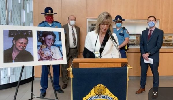 A white woman with blond hair in a white suit and an arm in a black sling speaks on a podium with the DPS logo and two photos of a teenage girl on an easel on the lefthand side of the image