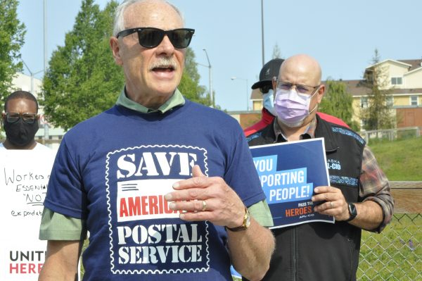 "A man in a blue t-shirt and sunglasses. His t-shirt reads ""Save America's Postal Service."" Behind him are people wearing masks holding placards."