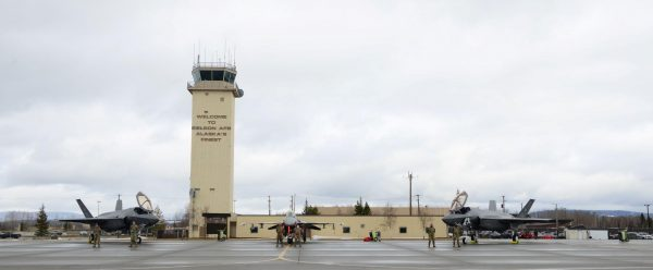Two f-35 fighter jets are parked in front of a beige aircraft control tower