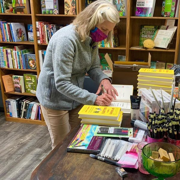 Author in a mask signing books with yellow covers.