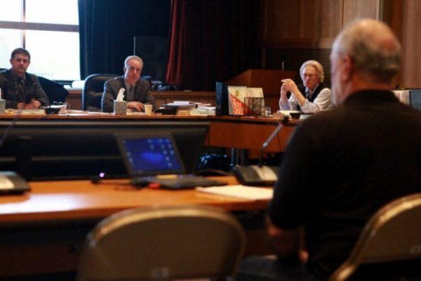 Several old white men on wooden desks talk seriously.