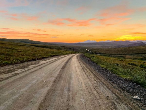 A dirt road leads into rolling mountains in a sunset