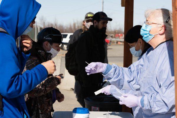 Un homme vêtu d'une blouse d'hôpital bleue et d'un masque chirurgical bleu passe un tampon à un homme vêtu d'un sweat à capuche bleu de l'autre côté de la table