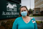 """A woman stands in front of a sign that reads """"Alaska Regional Hospital"""" and a building"""