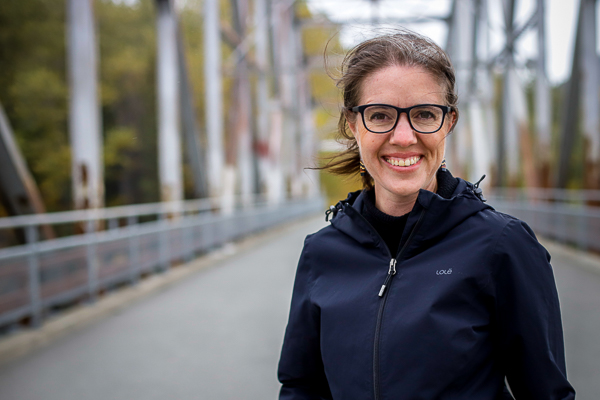 A woman smiles at the camera while standing on a bridge
