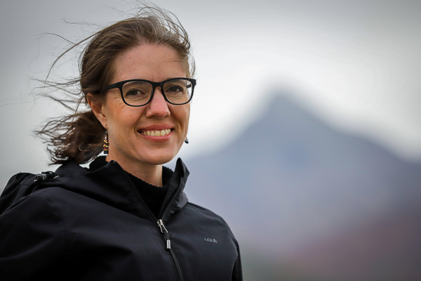 A woman smiles with mountains in the background