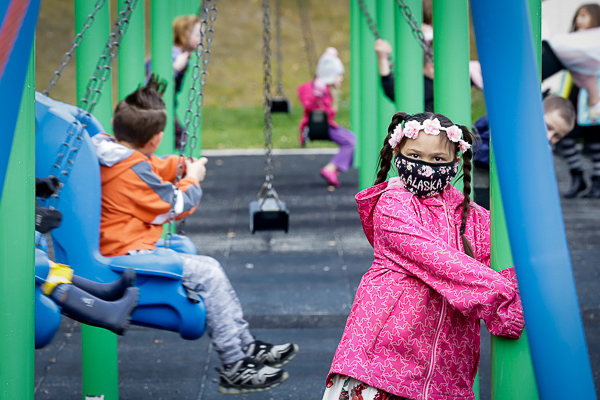 Child wears mask while other children swing on swing set