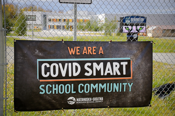 """a banner hung on a fence that reads """"we are a covid smart school community"""""""