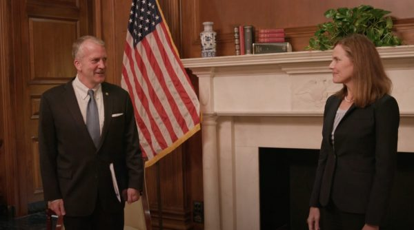 A man in a suit faces a woman in a suit. they are in a wood-paneled room in front of a fireplace with a U.S. flag beside it.