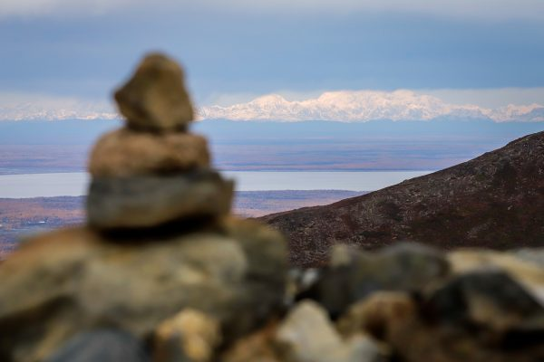 a blurry cairn in the foreground and a big mountain in the background