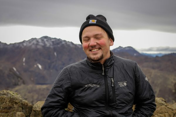 a person smiles in front of a mountain