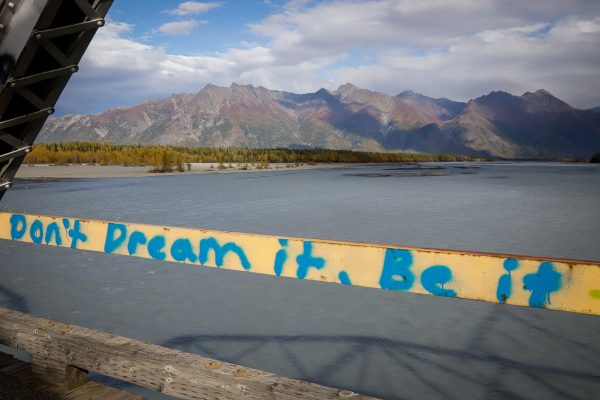 """A message that reads """"don't dream it, be it"""" in front of mountains and water"""